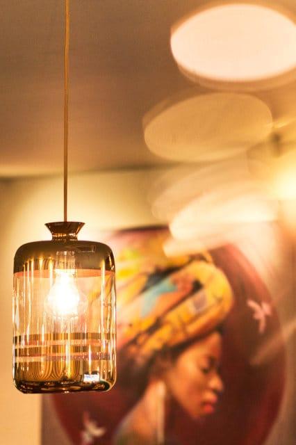 Pillar ceiling pendant against background of restaurant artwork