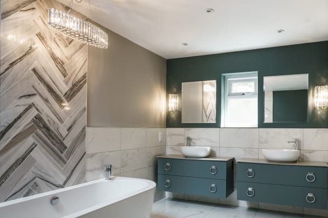 Kichler Crystal Skye chandelier and matching wall lamps shown in smart bathroom